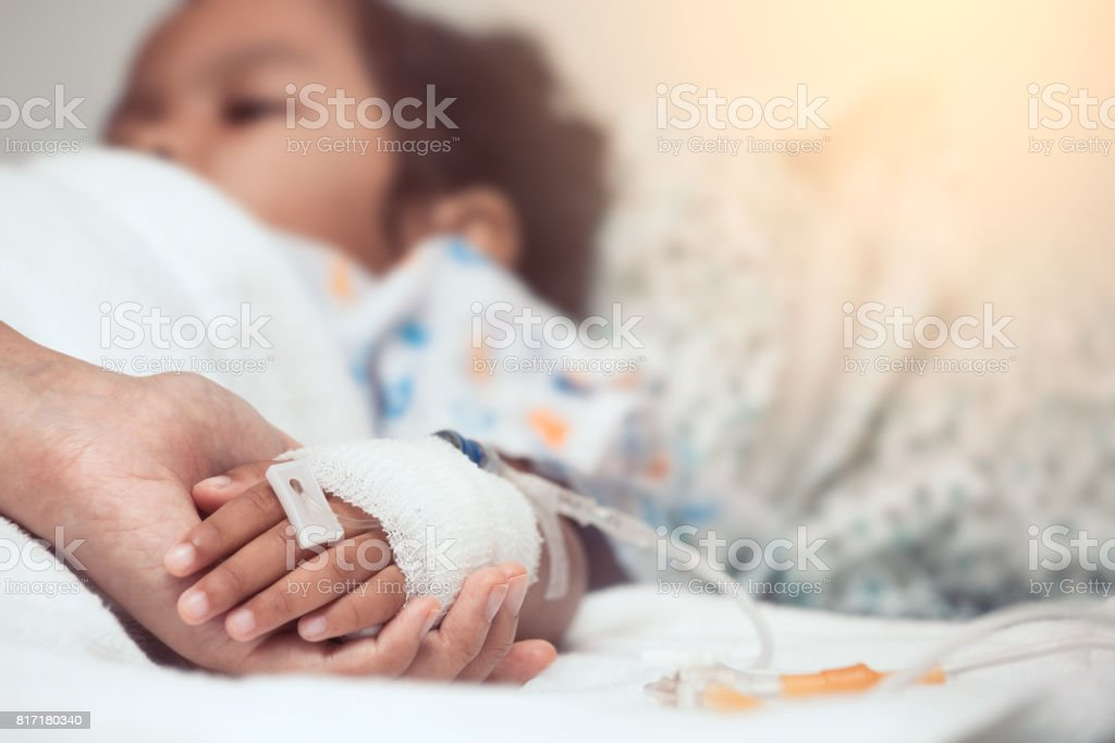 Mother hand holding child hand who have IV solution in the hospital with love and care - foto stock