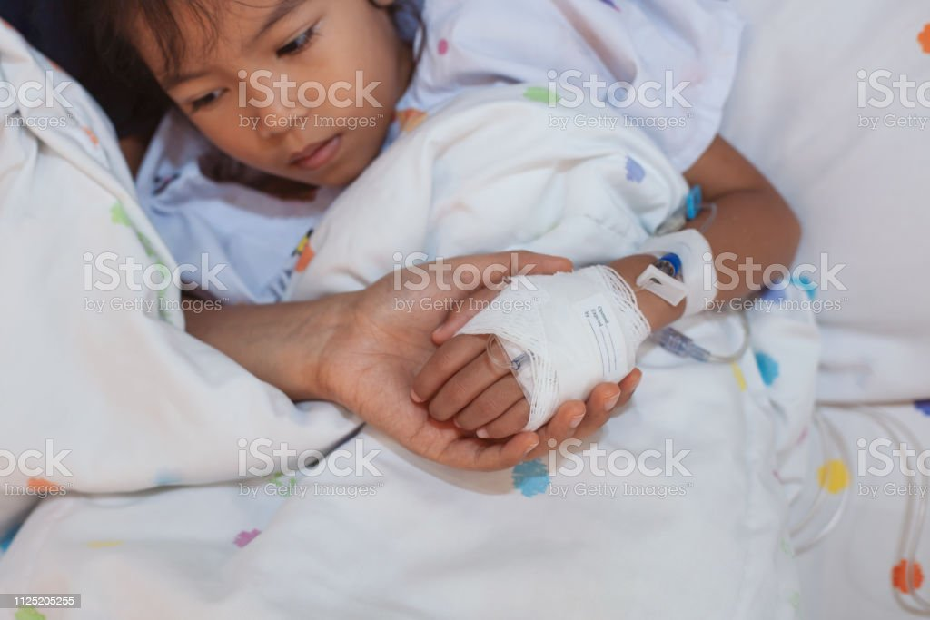 Mother hand holding sick daughter hand who have IV solution bandaged with love and care stock photo