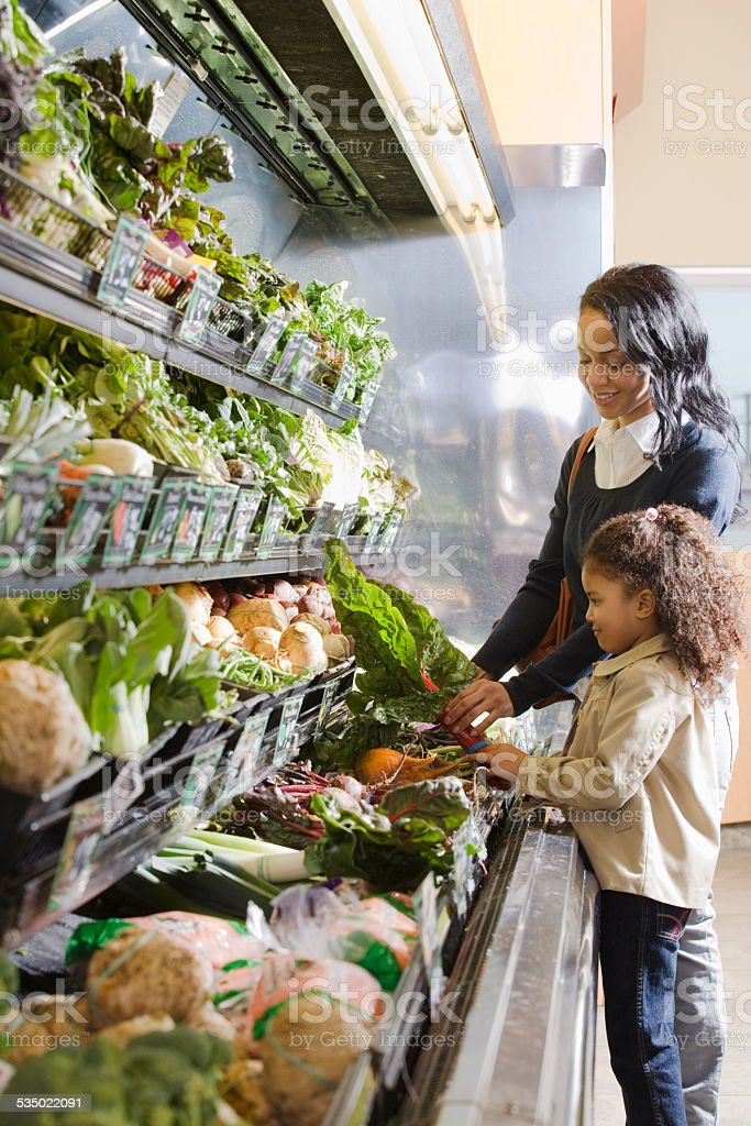 mother handing chard to her daughter stock photo