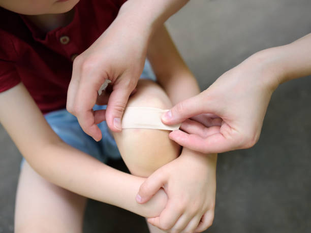 Mother hands applying antibacterial medical adhesive bandage on child's knee after falling down. stock photo