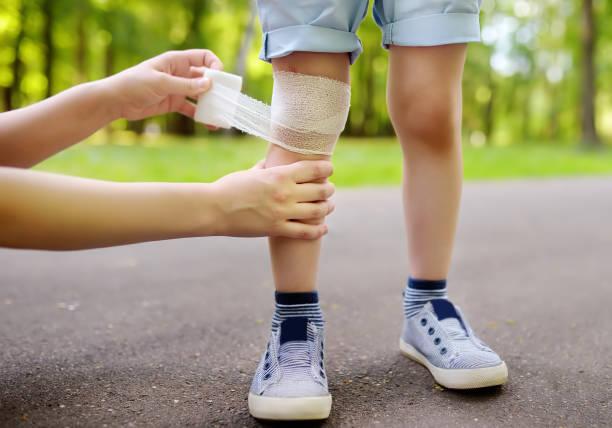 Manos madre aplicando vendaje médico antibacteriano en la rodilla del niño después de caerse. - foto de stock