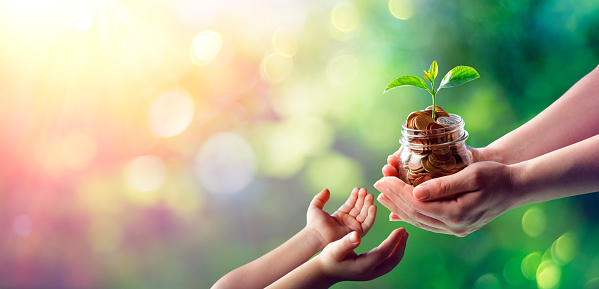 Hands of woman and child is holding coins in glass jar with young plant growing on money - family finance growth