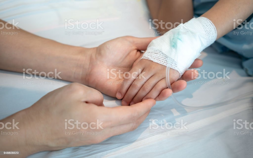 Mother hands holding her baby patient hand with Saline intravenous or (IV) drip. stock photo