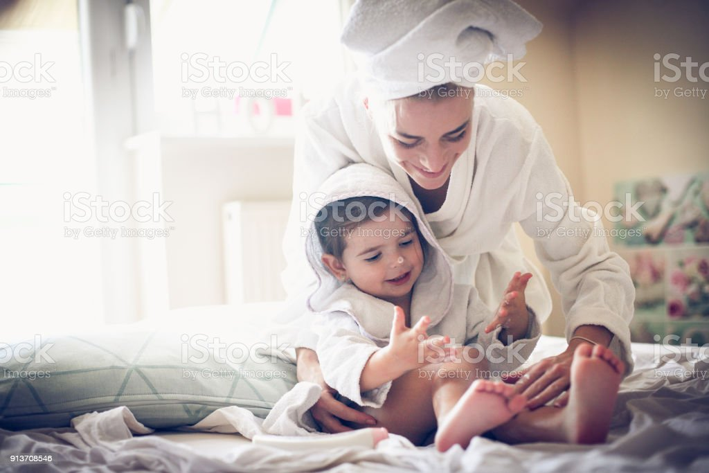 Mother have play with her little girl after bath. stock photo