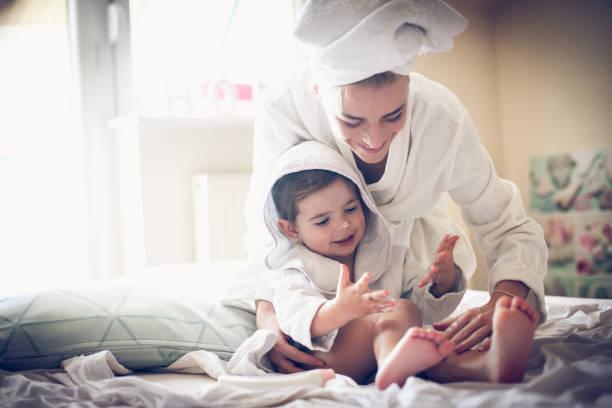 moeder heb spelen met haar kleine meisje na bad. - creme huid stockfoto's en -beelden