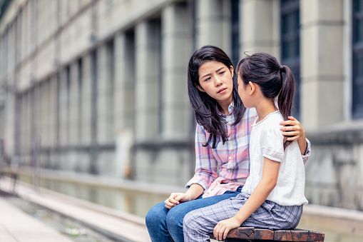 A woman is holding her arm around a young girl and is looking serious.