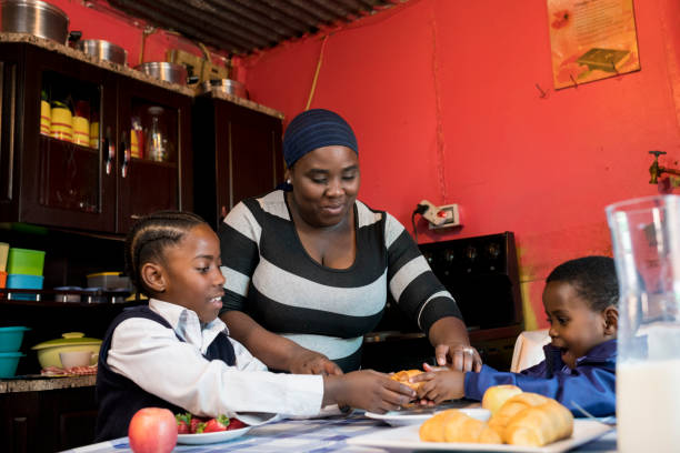 Mother having breakfast with her daughters stock photo