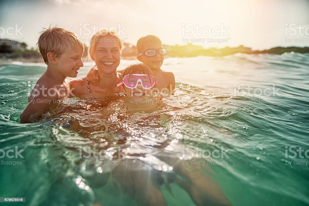 Mother having fun splashing in sea waves stock photo