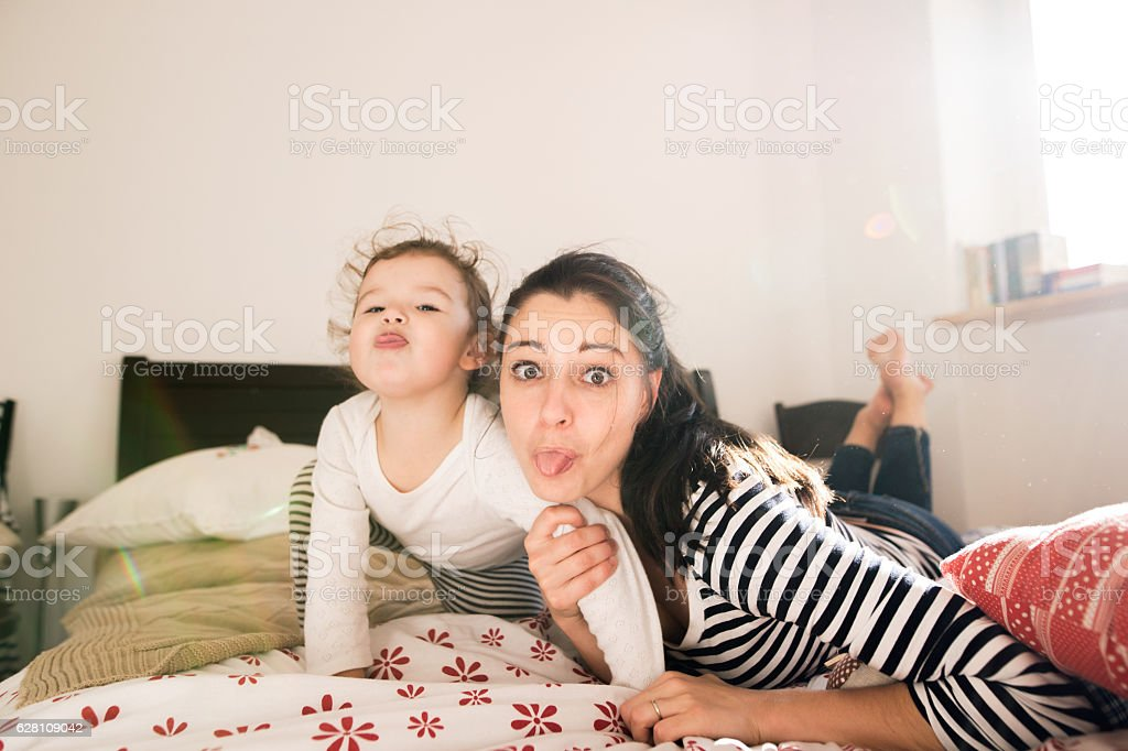 Mother having fun with her daughter in her bedroom stock photo