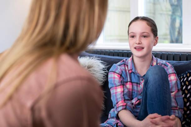 Mutter mit jungen Tochter zu Hause im Gespräch – Foto