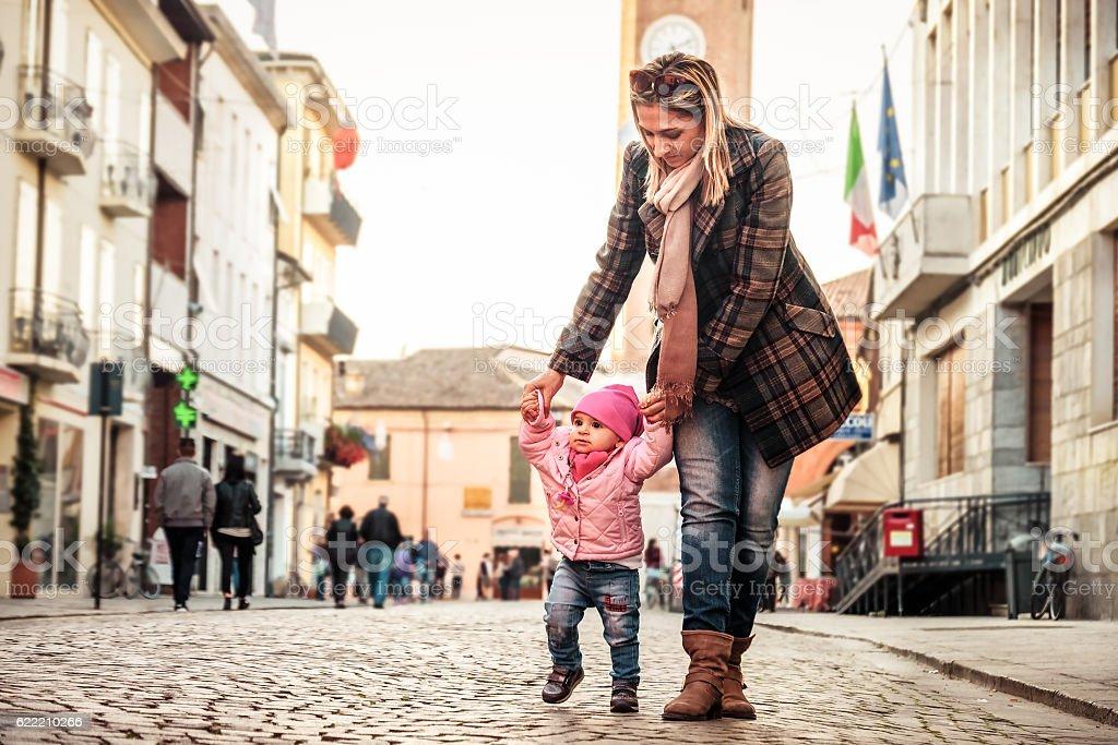 mother help baby walk stock photo