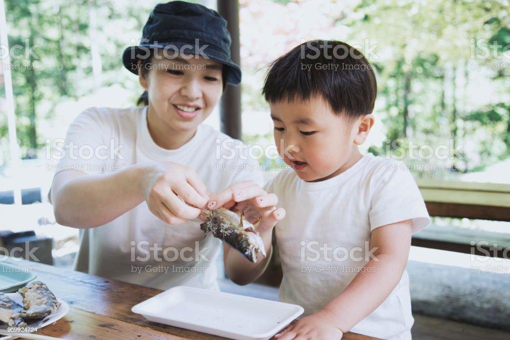 母は屋外焼き魚を食べる息子を助けるため ストックフォト