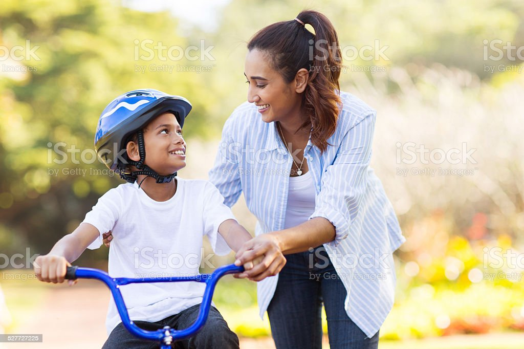 mother help her son ride a bicycle stock photo