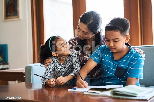istock Mother helping children in studies at home 1034353548