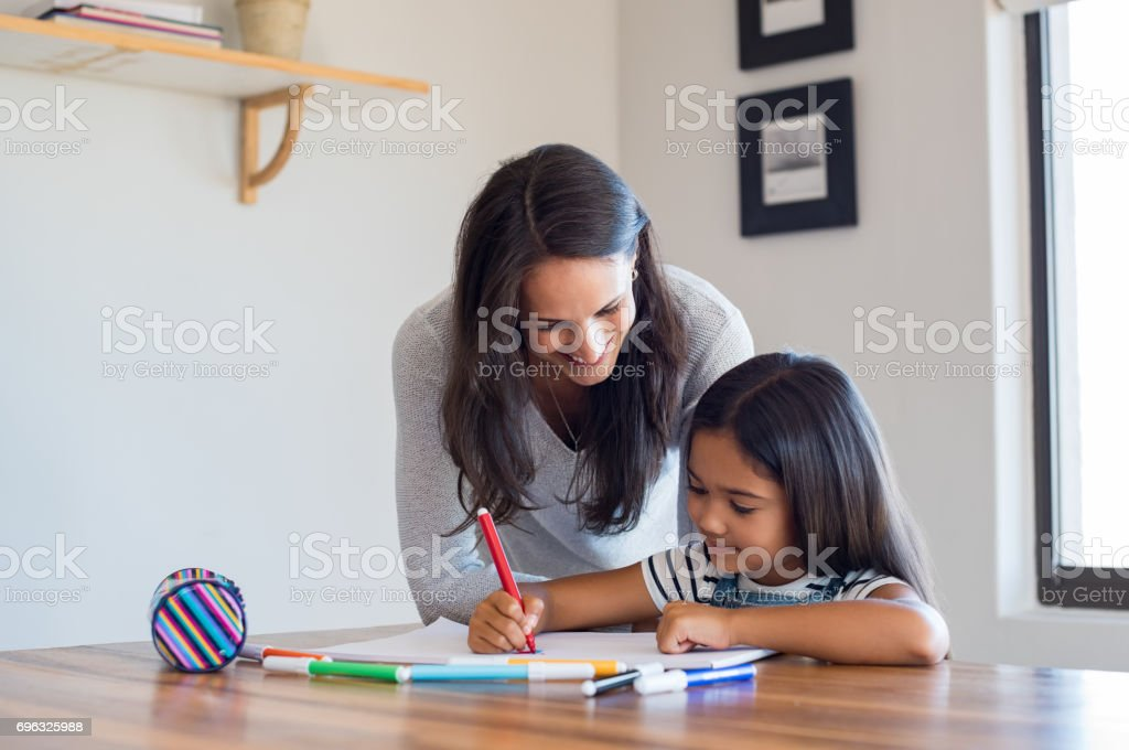 Mother helping daughter draw stock photo