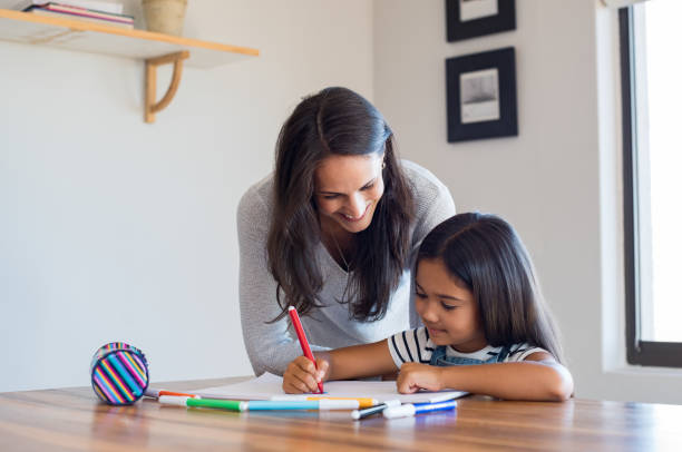 mother helping daughter draw - homework stock photos and pictures