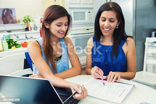 Mother and teenage daughter are in the kitchen researching colleges and filling out university applications.