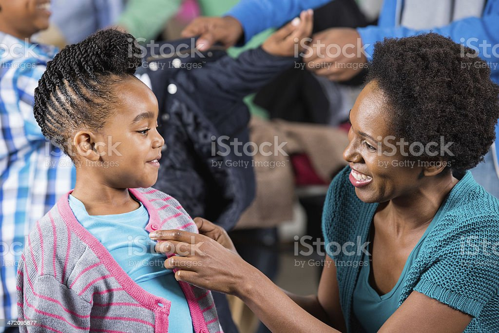 Mother helping daughter find clothes at winter clothing drive royalty-free stock photo