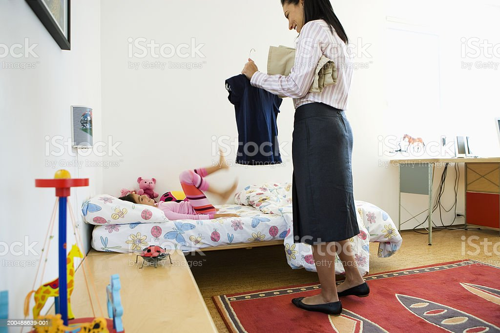 Mother helping daughter (5-7) get out of bed and dressed royalty-free stock photo