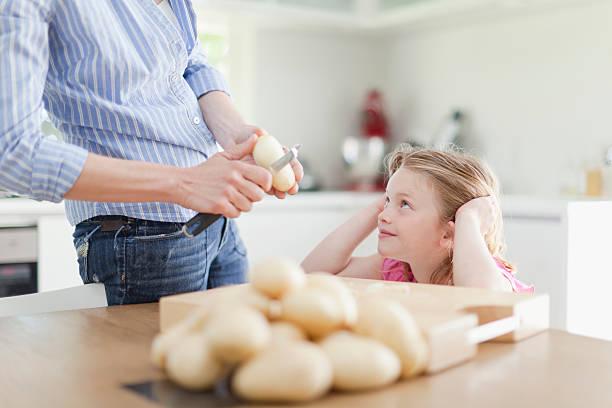 mutter hilft tochter peel kartoffeln - peeling zu hause machen stock-fotos und bilder