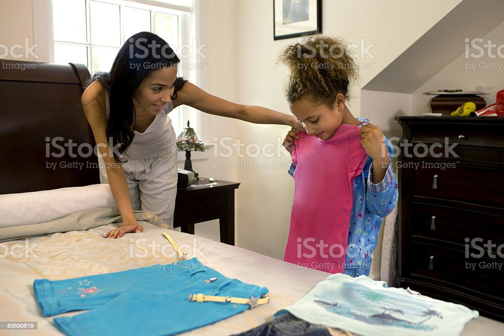 Mother helping daughter pick outfit stock photo