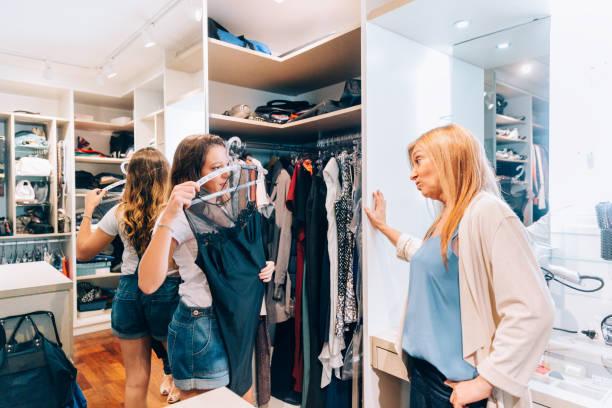mutter hilft tochter bei der wahl eines kleides - mutterkleiderschrank stock-fotos und bilder
