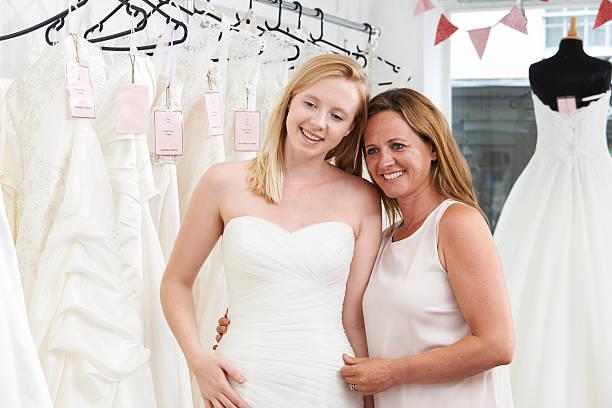 mutter hilft ihrer tochter für sie kleid in bridal shop - mütterbrautkleider stock-fotos und bilder