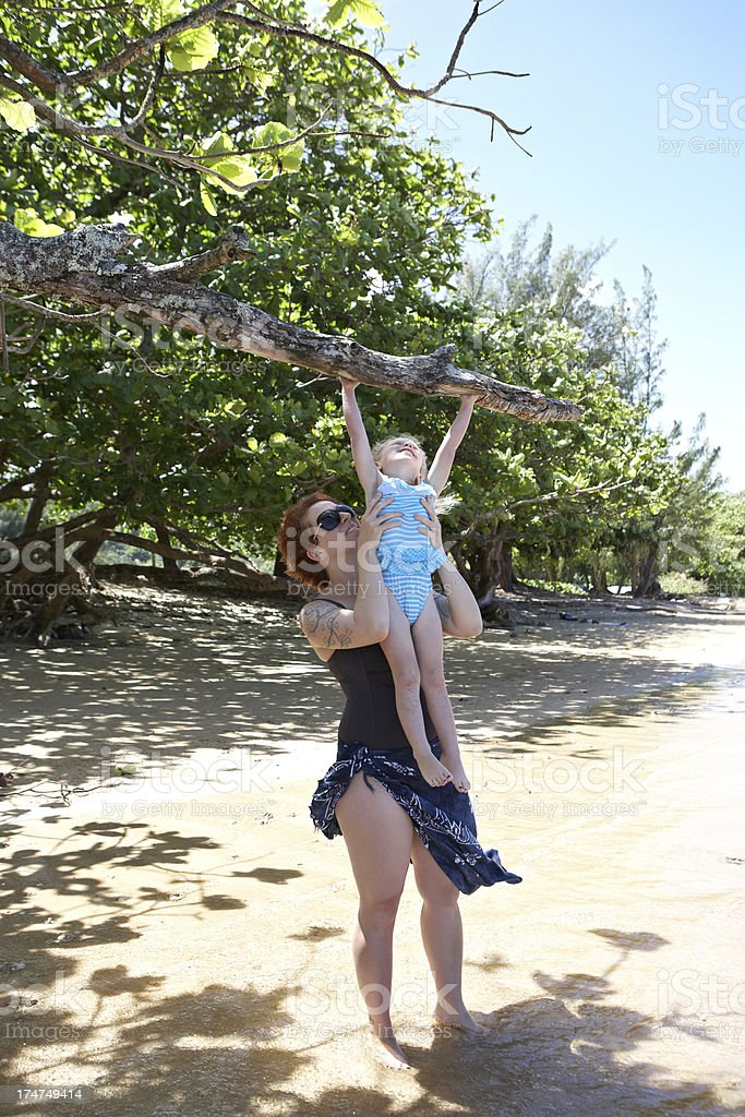 Mother helping daughter up into tree royalty-free stock photo