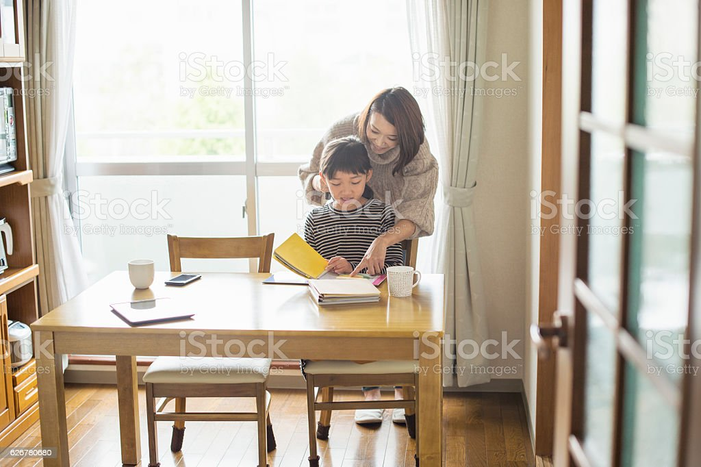 Mother helping daughter with homework in dining room stock photo