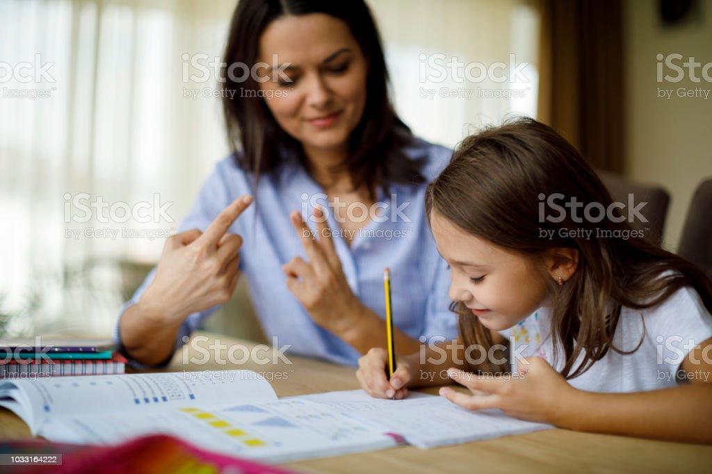 Mutter ihre Tochter bei Hausaufgaben helfen – Foto