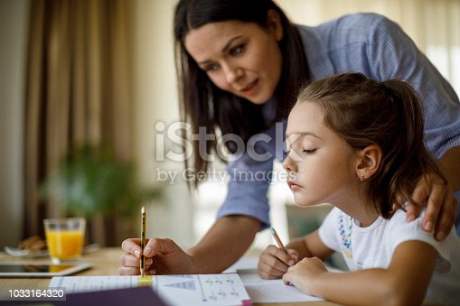 istock Mother helping daughter with homework 1033164320
