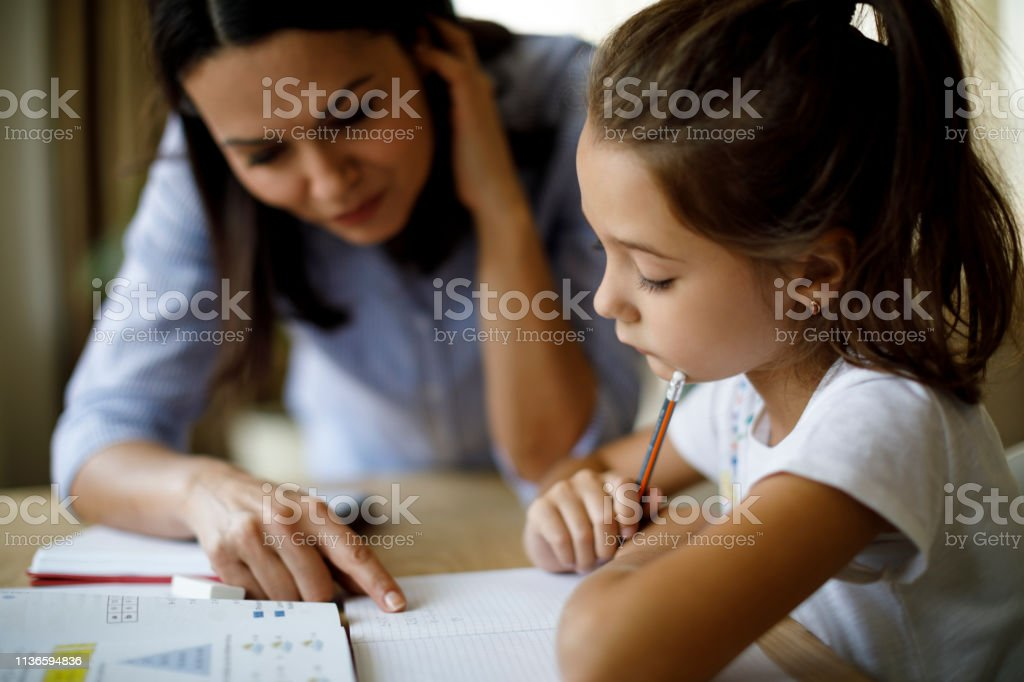 Mother helping daughter with homework Mother helping daughter with homework A Helping Hand Stock Photo