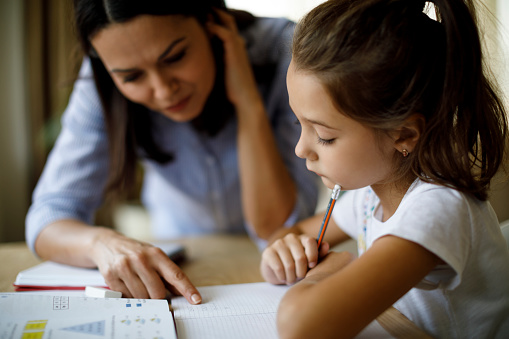 Mother Helping Daughter With Homework Stock Photo - Download Image Now