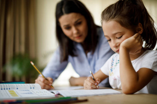 Mother helping daughter with homework stock photo