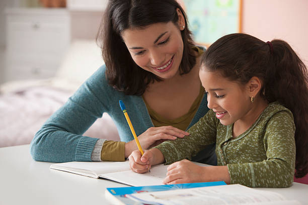 mother helping daughter with homework - homework stock photos and pictures