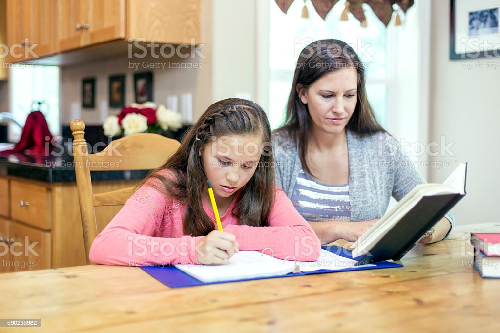 Mother helping daughter with homework royaltyfri bildbanksbilder