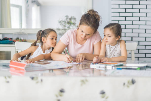 Mother helping daughters with homework Mother helping daughters with homework homework stock pictures, royalty-free photos & images