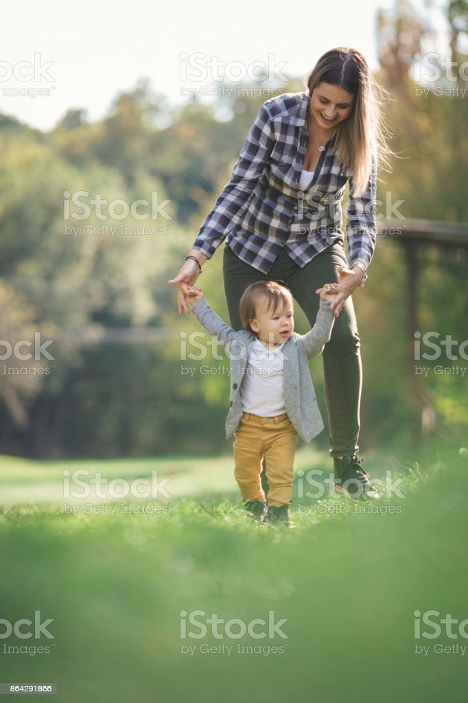 Mother helping her baby boy to walk royalty-free stock photo
