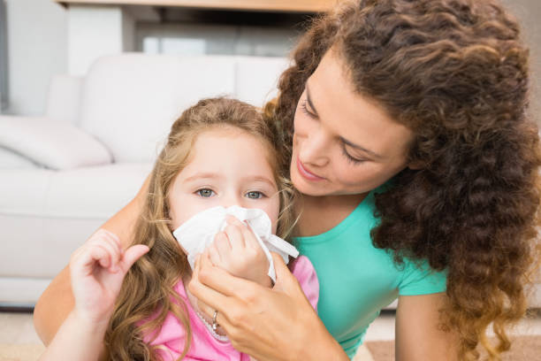 Mother helping her daughter blow her nose Mother helping her daughter blow her nose at home in living room human parainfluenza virus stock pictures, royalty-free photos & images