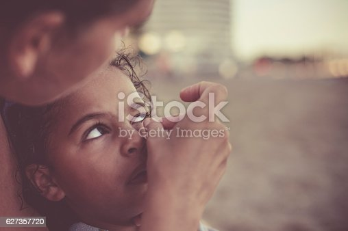 Stock photo of a mother who is removing sand that got into her daughter's eye while playing on the beach. This file has signed model releases.