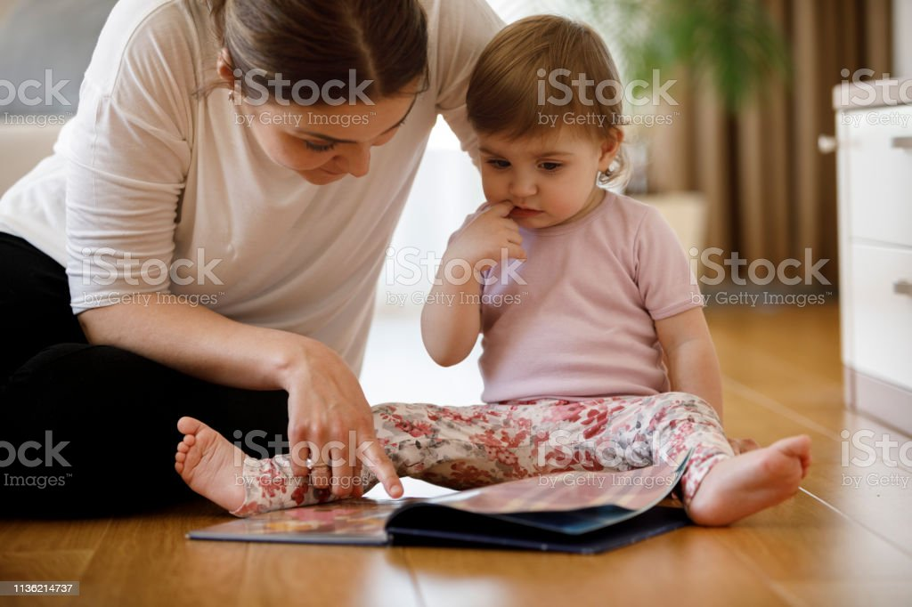 Mother helping her daughter while studying - Royalty-free 12-23 Months Stock Photo