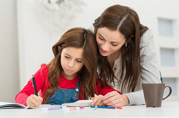 mother helping her daughter while studying - homework stock photos and pictures