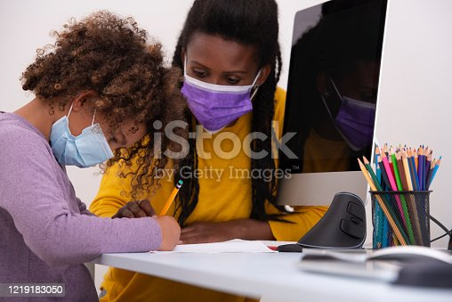 Mother and her girl wearing a cloth face-covering due to social distancing can't be practiced. A six-year-old schoolgirl studying one-on-one with a mother and online with the rest of the class pupils, using a computer, pencils, and notebook, sitting at the table. Digital online education concept during the Coronavirus pandemic.