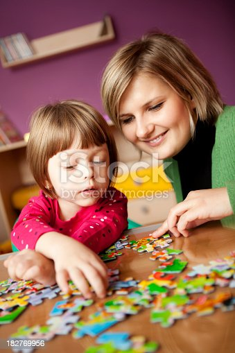 istock Mother helping her daughter with puzzle 182769956