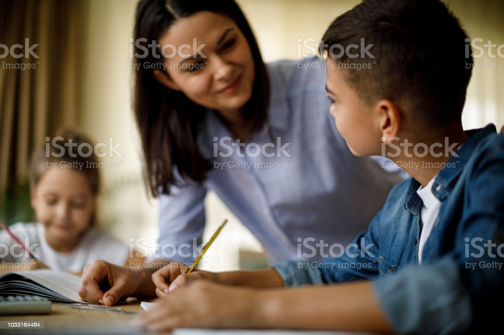 Mother helping her kids with homework