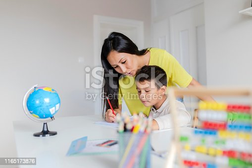 istock Mother Helping Her Little Son With Homework 1165173876