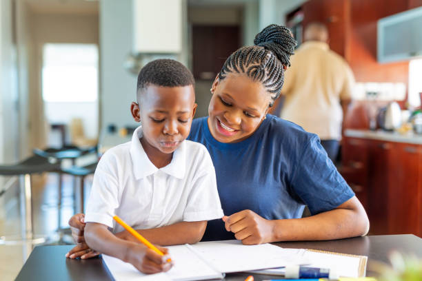 Mother Helping Her Son Do Homework at the Dining Room Table stock photo