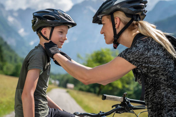 Mother helping her son fasten his cycling helmet