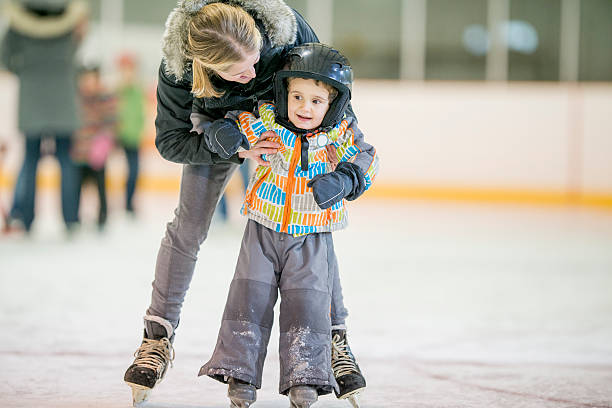 Mother Helping Her Son Learn to Ice Skate A mother is at the skating rink with her son teaching him how to ice skate. She is holding him up and supporting him so he doesn't fall. ice rink stock pictures, royalty-free photos & images