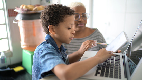 Mother helping her son studying with laptop on a online class at home